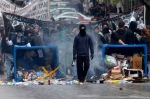 A protester carries a petrol bomb during a protest at the northern port city of Thessaloniki, Greece, Tuesday, Dec. 6, 2011. Protesting high school students hurled rocks and bottles during a rally to mark the third anniversary of the fatal police shooting of a teenager in central Athens. (AP Photo/Nikolas Giakoumidis)